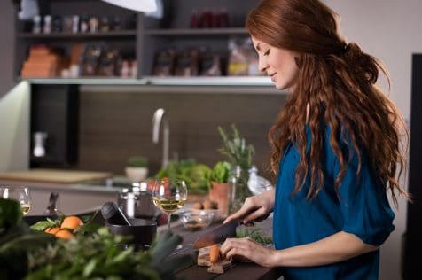 Happy young woman cutting carrots in kitchen. Happy woman cooking vegetables salad in kitchen.