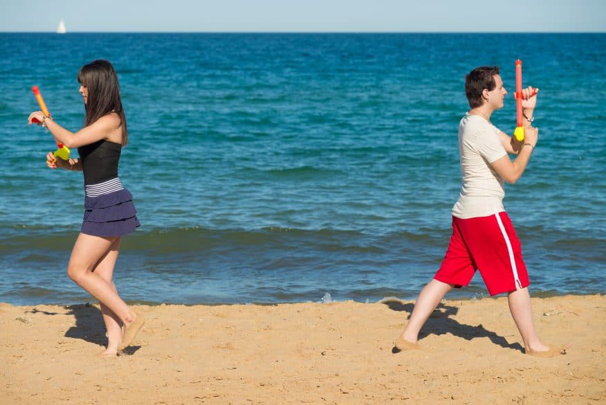 Couple walking away from each other to start a water gun duel