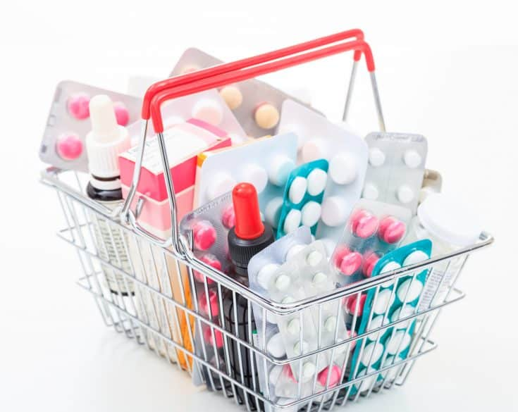 Basket with colorful pills on white background