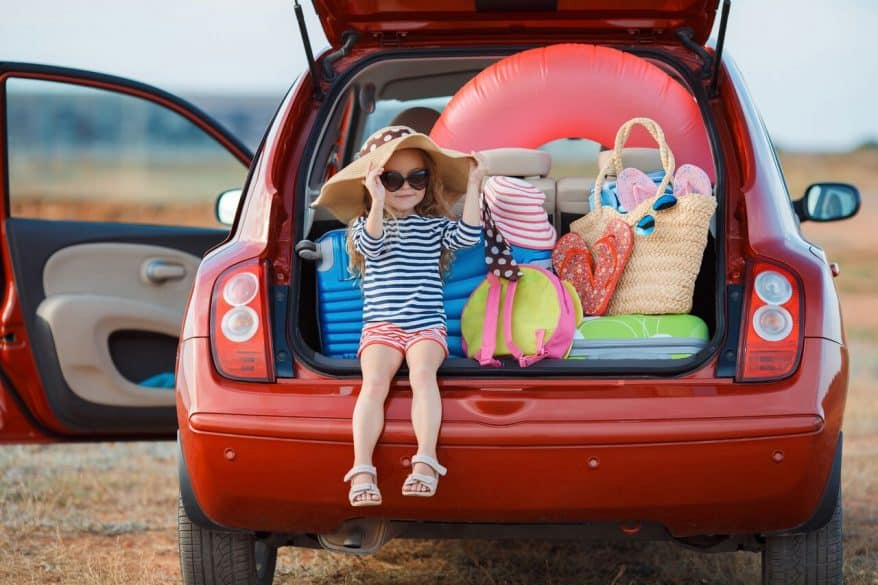 little girls sitting in the back of car at the beach