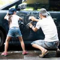 father and child washing car