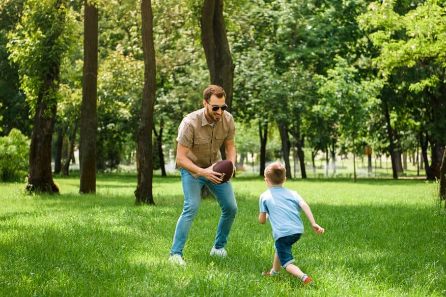 father son playing football