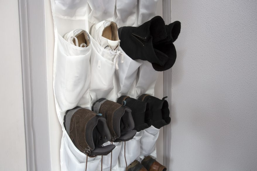 Shoe rack hanging on a wooden door, storage for shoes close-up shoe organization ideas