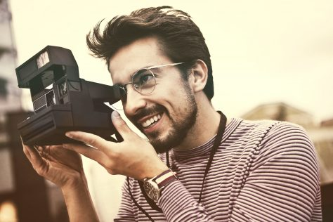 man taking pictures with polaroid camera