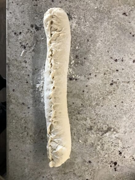 French bread dough rolled up with the seams pinched and end tucked.