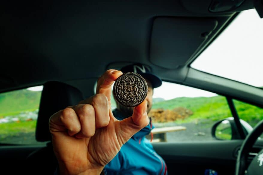 A man holding up an Oreo between two fingers.