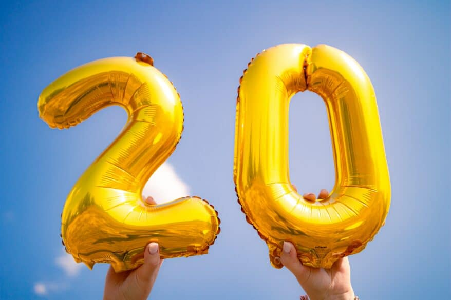 The number 20 in gold mylar balloons being held up in the air.