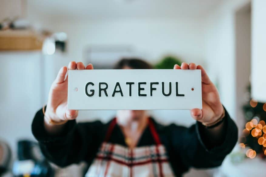 """A person holding up a sign that says """"GRATEFUL""""."""