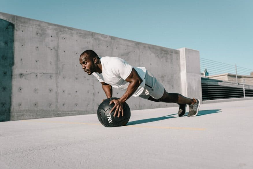 Man doing a plank with his hands on a ball.