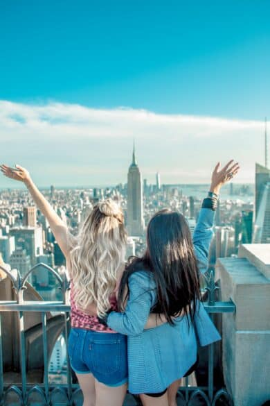 Two girls looking out over a city with one arm around each other and the other in the air.