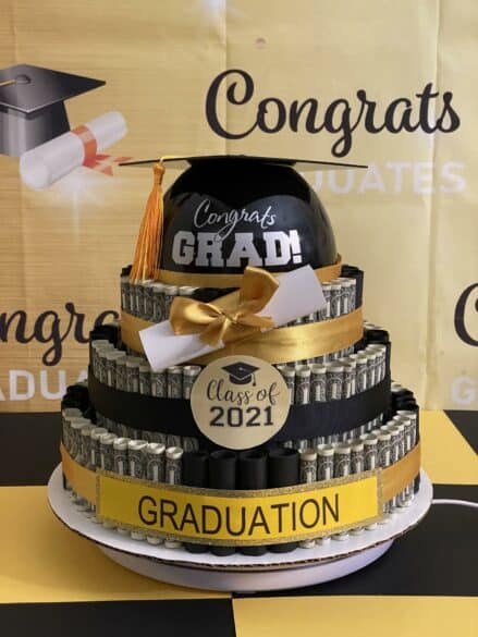 A 3 layered money cake in black and gold.