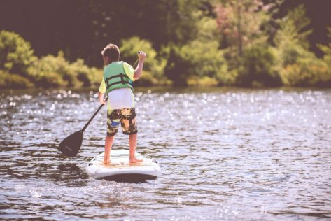 Boy paddleboarding staycation activity ideas