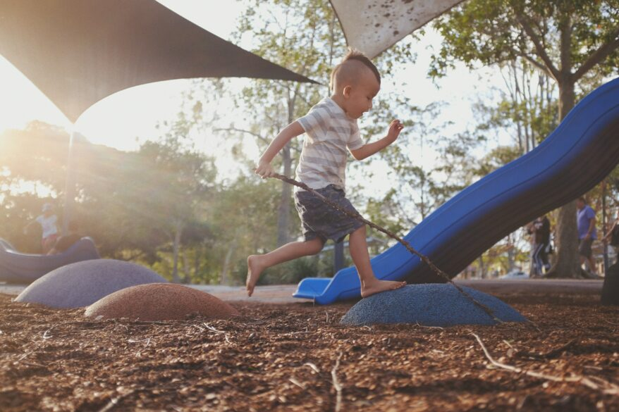 Boy jumping across toys at a playground.
