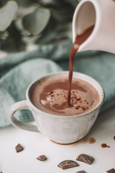Hot chocolate being poured into a tea cup.
