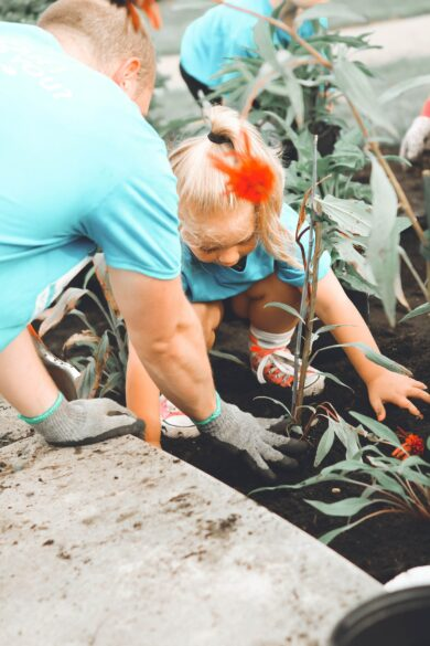 Little girl planting a flower.