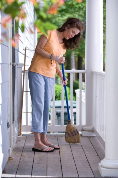 Woman sweeping a porch.